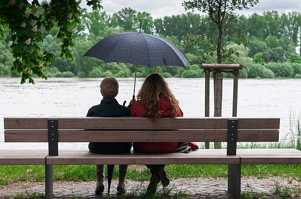 Women with umbrella on a bench stock photo