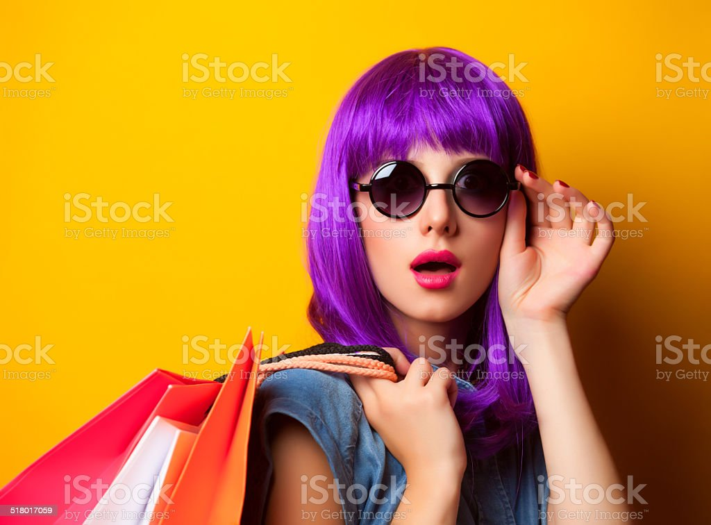 Women with violet hair with shopping bags. stock photo