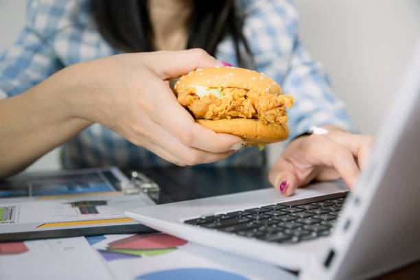 Women work and eat hamburgers to eat lunch in office stock photo
