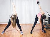 Two caucasian women doing windmills in gym