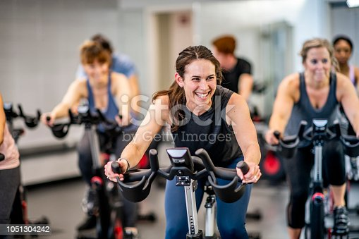 A group of adults are indoors in a fitness center. They are riding exercise bikes. One woman is smiling in the foreground.