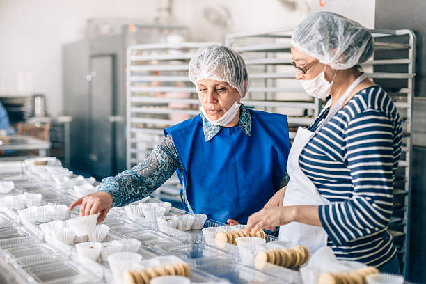 women working together at bakery workshop - mexikanisch kochen stock-fotos und bilder