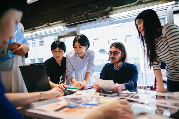 Women working together in modern working space Group of people are working together in a modern working space in Tokyo. japanese ethnicity stock pictures, royalty-free photos & images