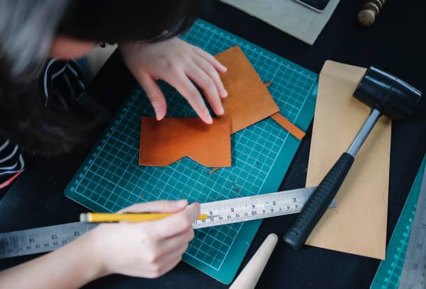 frauen arbeiten mit leder mit handwerklichen werkzeugen - diy leder stock-fotos und bilder