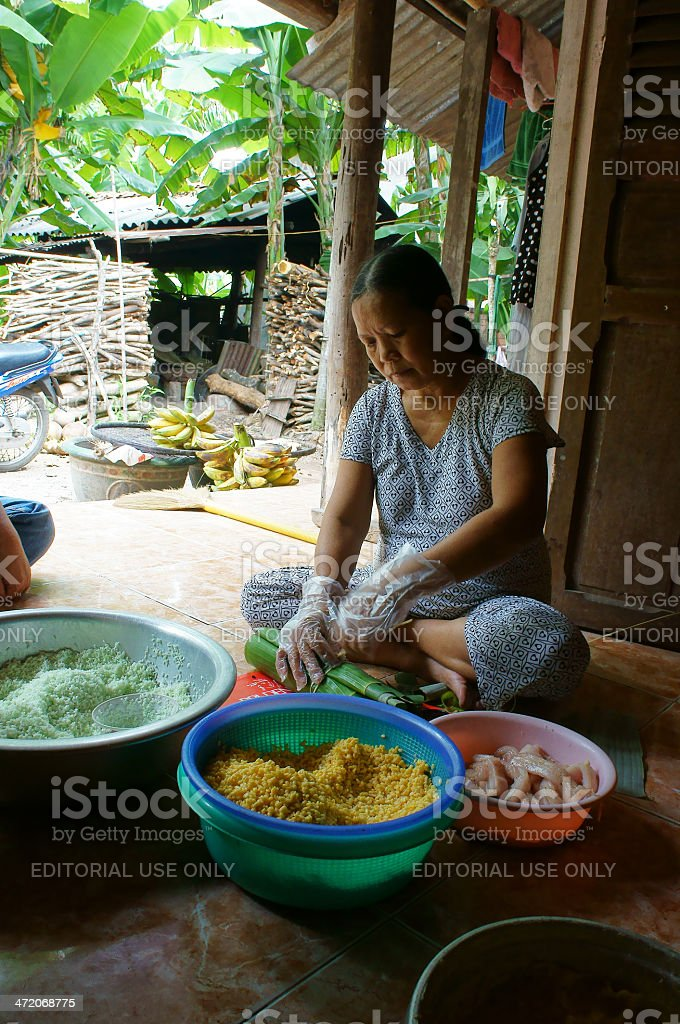 Women wrap up Cylindric glutinous rice cake (banh tet) stock photo