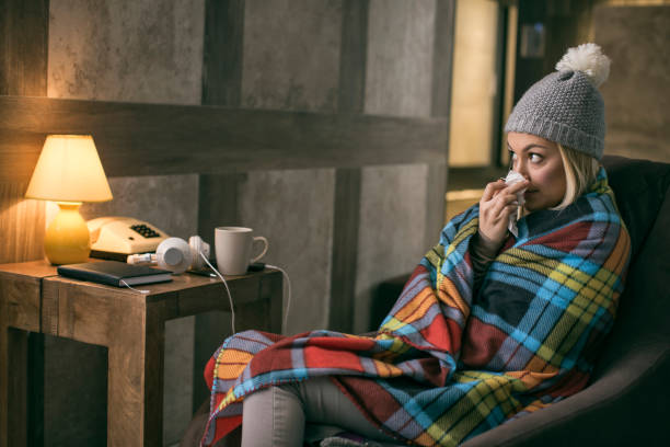 Women wrapped at blanket having flu at home Young blonde women wrapped at blanket having flu at home wrapped in a blanket stock pictures, royalty-free photos & images