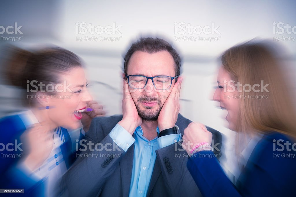 Women yelling at businessman who covered ears with his hands foto de stock libre de derechos