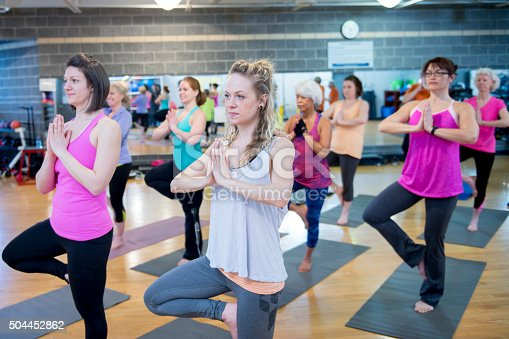 A multi-ethnic group of women are taking a yoga class together at the gym.