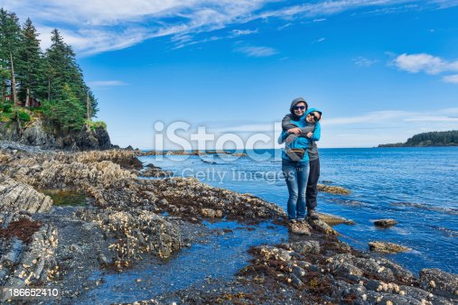 Happy mother is embraced by son in the moment of walk at the seaside. Kodiak island , Alaska.