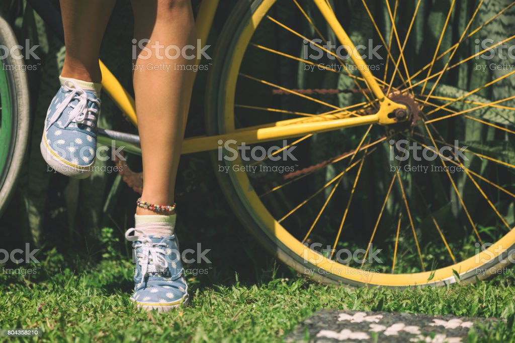 Women's beautiful legs standing with old bicycle outdoors. stock photo