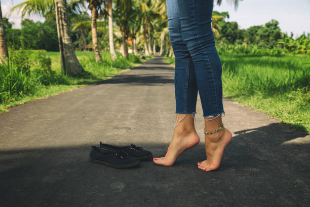 Women's beautiful legs with canvas shoes on the road. stock photo