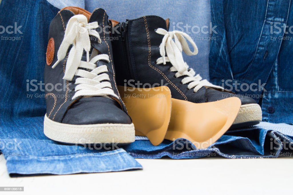 women's blue boots with a white lacing with orthopedic insoles. Background  of blue sweatshirt stock photo