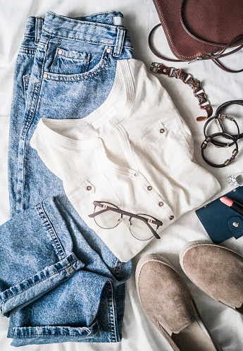 640200626 istock photo Women's clothes set - mom's jeans, suede sneakers, cotton t-shirt, leather bag, bracelets, lipstick on a light background, top view. Beauty, fashion concept. Flat lay 1136174633