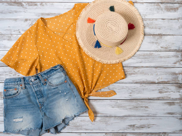 womens clothing, accessories  ( denim shorts, yellow blouse in polka dot, straw hat). fashion outfit, spring summer collection. shopping concept. flat lay, view from above - spring fashion stock pictures, royalty-free photos & images