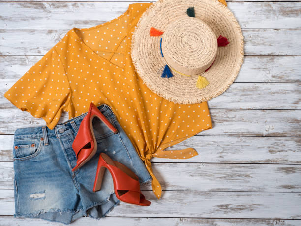 Womens clothing, accessories, footwear (leather mule heels shoes, denim shorts, yellow blouse in polka dot, straw hat). Fashion outfit, spring summer collection. Shopping concept. Flat lay, view from above stock photo