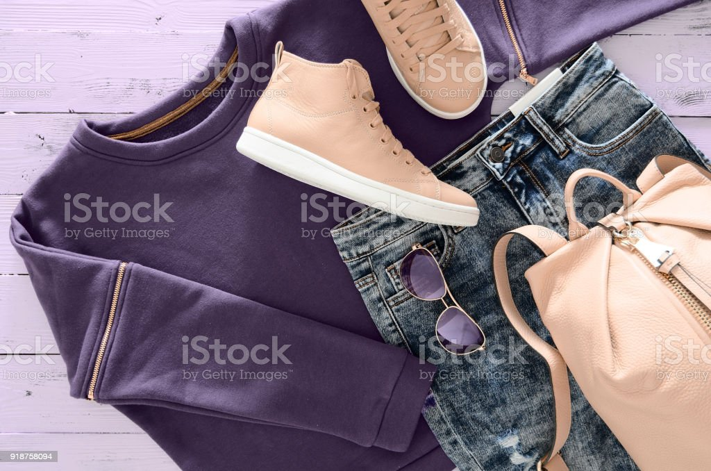 Womens clothing, accessories, footwear (violet sweatshirt, acid washed jeans,  leather backpack and sneakers, sunglasses) on wooden background. Outfit for teens. Top view, flat lay. Trendy colors stock photo