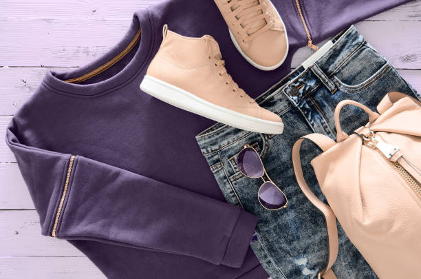 Womens clothing, accessories, footwear (violet sweatshirt, acid washed jeans,  leather backpack and sneakers, sunglasses) on wooden background. Outfit for teens. Top view, flat lay. Trendy colors Womens clothing, accessories, footwear (violet sweatshirt, acid washed jeans,  leather backpack and sneakers, sunglasses) on wooden background. Outfit for teens. Top view, flat lay. Trendy colors hood clothing stock pictures, royalty-free photos & images
