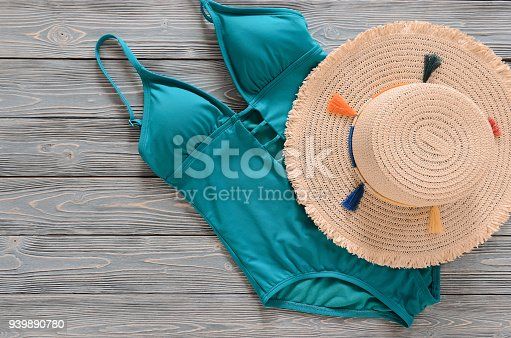 Womens clothing, accessories (straw hat, blue green swimsuit) on grey wooden background with copy space. Trendy fashion outfit. Shopping, travel, summer, beach concept, abstract.  Flat lay