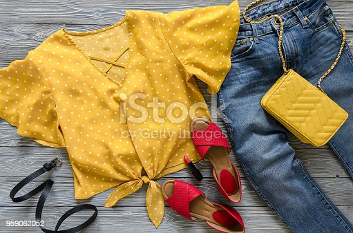 Womens clothing, accessories, shoes (yellow blouse in polka dot, blue jeans, leather red sandals,  yellow crossbody bag, lipstick). Fashion outfit. Shopping concept. Flat lay. Trendy, saturated colors. Spring summer collection