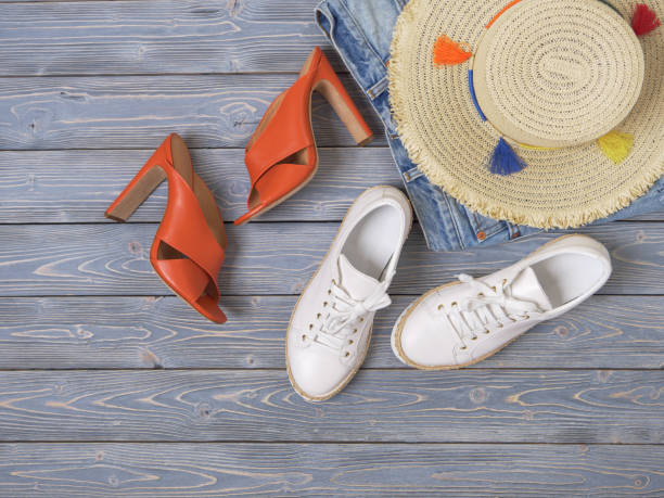 Womens clothing, accessories, shoes (denim shorts, straw hat, heel sandals, sneakers). Fashion outfit, spring summer collection. Shopping concept. Flat lay, view from above stock photo