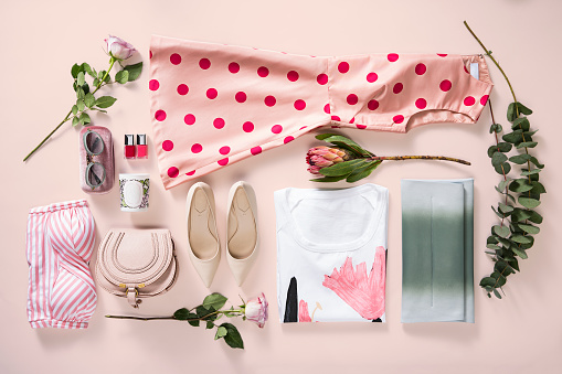 Women's clothing and personal accessories isolated on pink background