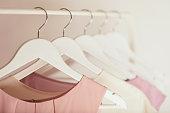 白いハンガーにピンクの色調で婦人服。