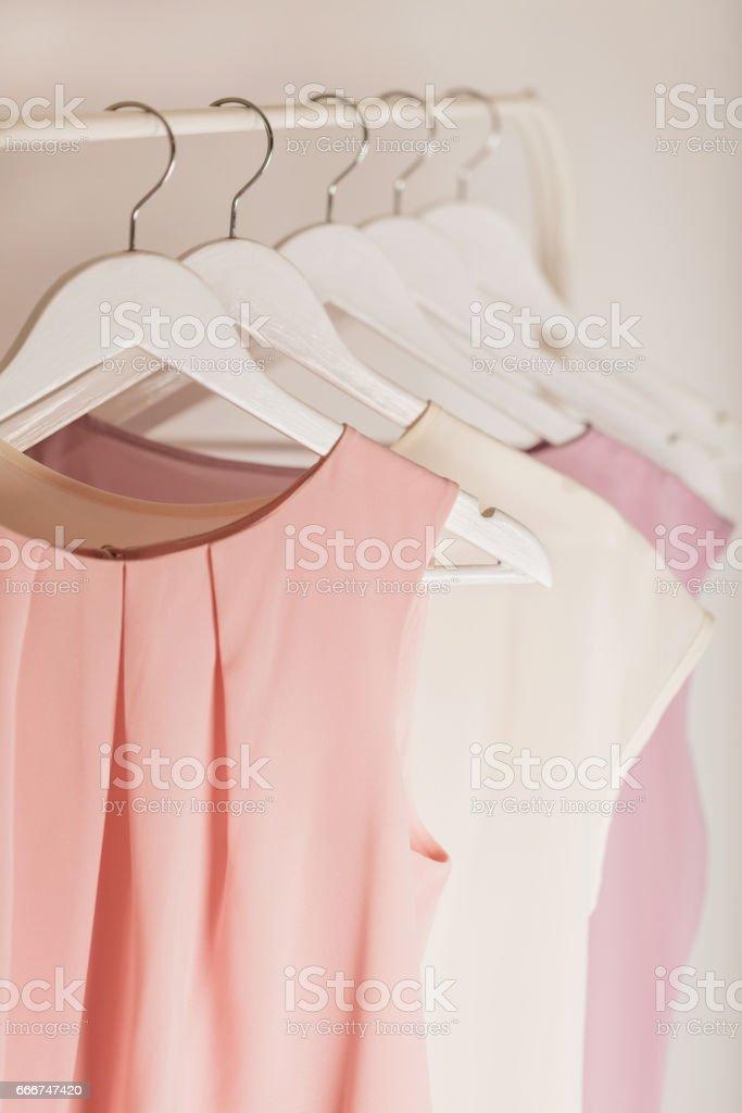 Damenbekleidung in rosa Tönen auf einem weißen Bügel. – Foto