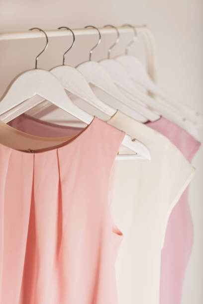 Women's clothing in pink tones on a white hanger. stock photo