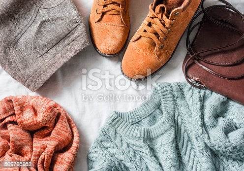 istock Women's clothing set - skirt, suede boots, sweater, scarf, leather cross body bag on a light background, top view. Winter, fall female clothing 869765652