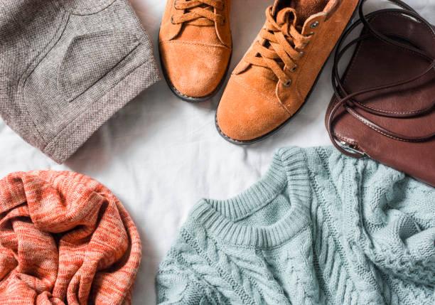 zestaw odzieży damskiej - spódnica, zamszowe buty, sweter, szalik, skórzana torba na ciało na jasnym tle, widok z góry. odzież zimowa, jesienna - akcesorium osobiste zdjęcia i obrazy z banku zdjęć