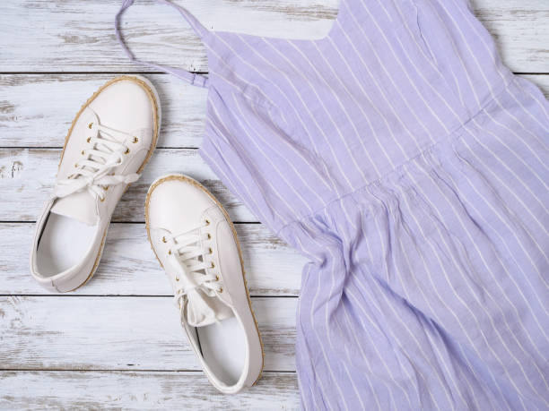 Womens clothing, shoes, accessories (lavender dress, white leather sneakers). Fashion outfit, spring summer collection. Shopping concept. Flat lay, view from above stock photo