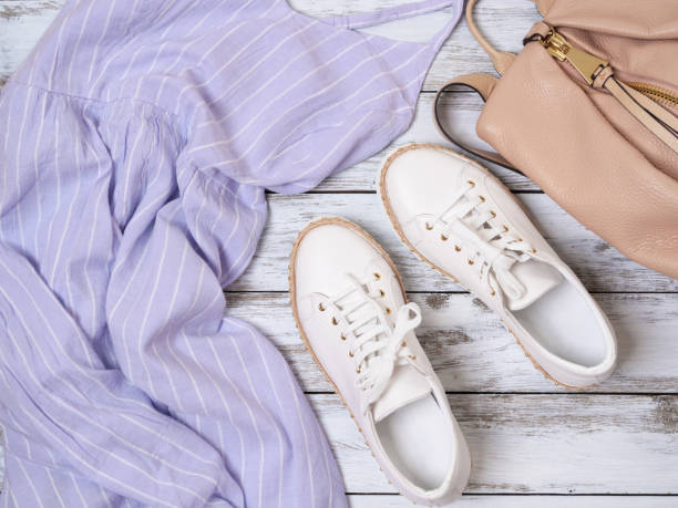 Womens clothing, shoes, accessories (lavender dress, white leather sneakers, beige backpack). Fashion outfit, spring summer collection. Shopping concept. Flat lay, view from above stock photo