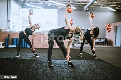 An exercise class goes through a training routine in a small gym.  They use kettlebells for a strength training routine.