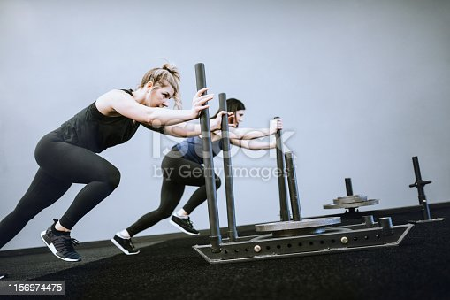 An exercise class goes through a training routine in a small gym.  They push weighted sleds with looks of determination.