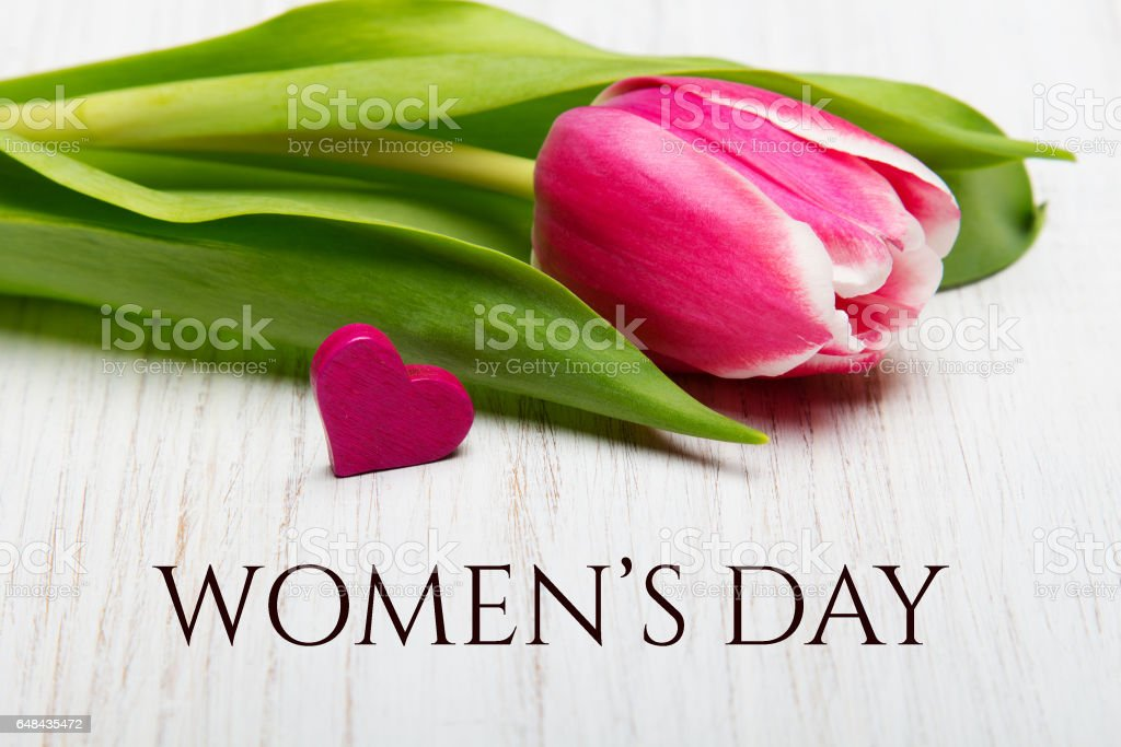 Women's day card.Tulip flower and heart on white wooden background. stock photo