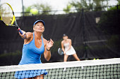 Mature woman hitting a forehand winner in doubles match.