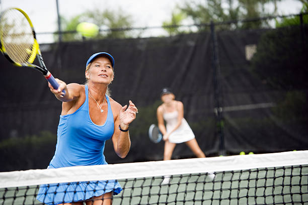 womens doubles match tennis volley - tennis stock photos and pictures