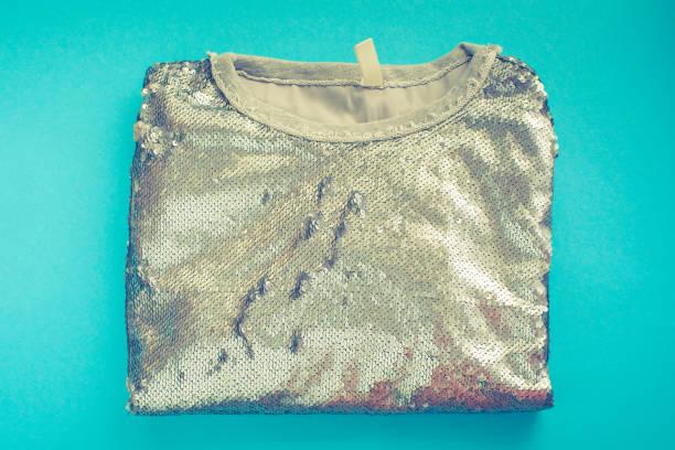 elegante damen sweatshirt liegt auf einem blauen hintergrund draufsicht glänzende textur dekor pailletten mode - pailletten shirt stock-fotos und bilder