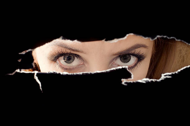 women's eyes spying through a hole - female spy stock photos and pictures