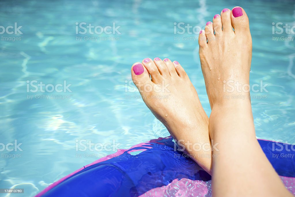 women's feet relaxing on float stock photo