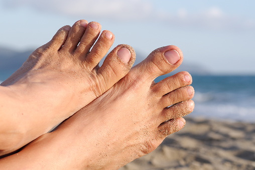 Womens Feet With Natural Nails With A Beach Background - Fotografie stock e altre immagini di Adulto