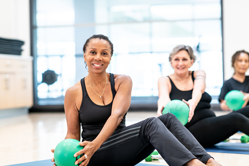 A multi-ethnic group of middle aged women sit on a gym floor on yoga mats, with their legs bent and out in front of them.  They each have a small green ball in their hands as they twist fro side to side. They are all dressed in comfortable, black fitness clothing and smiling.