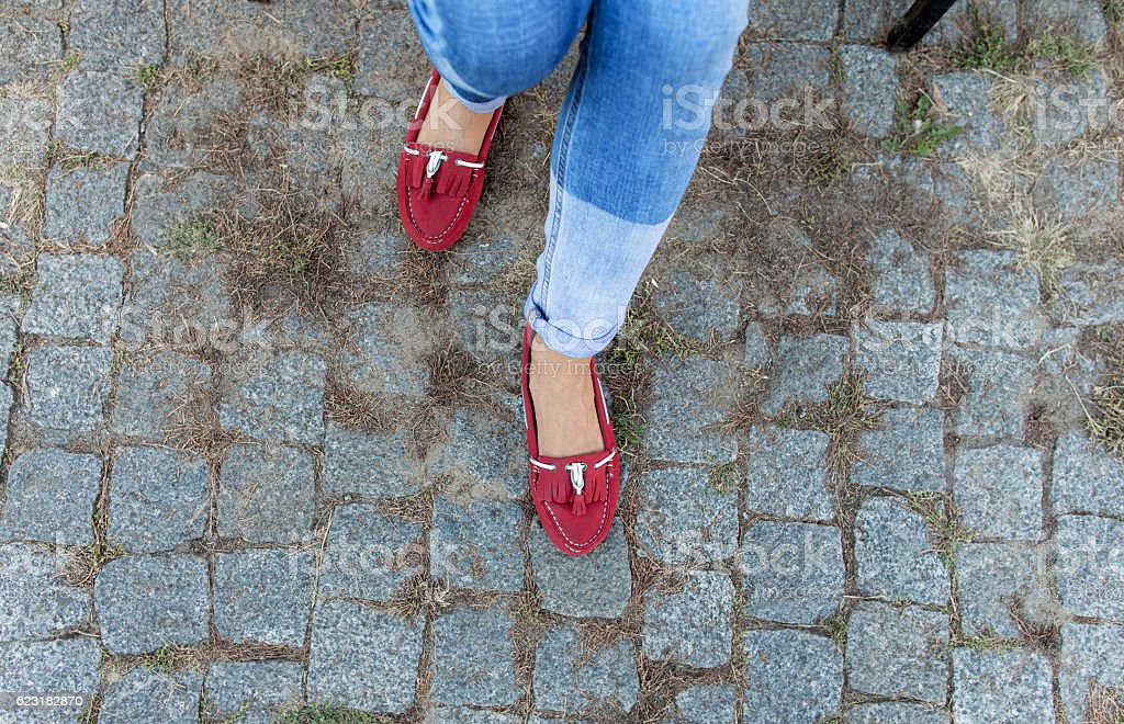 Womens foot close up in jeans and red loafers stock photo