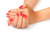 Women's hand clasped together showing off red manicure