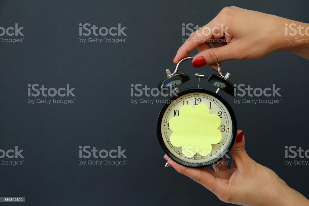 Women's hand holding alarm clock with sticky paper stock photo