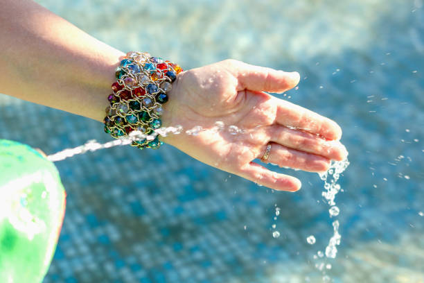 frauen hand, spielen mit sauberem und frischem wasser spritzt, in einen brunnen. - armband water stock-fotos und bilder