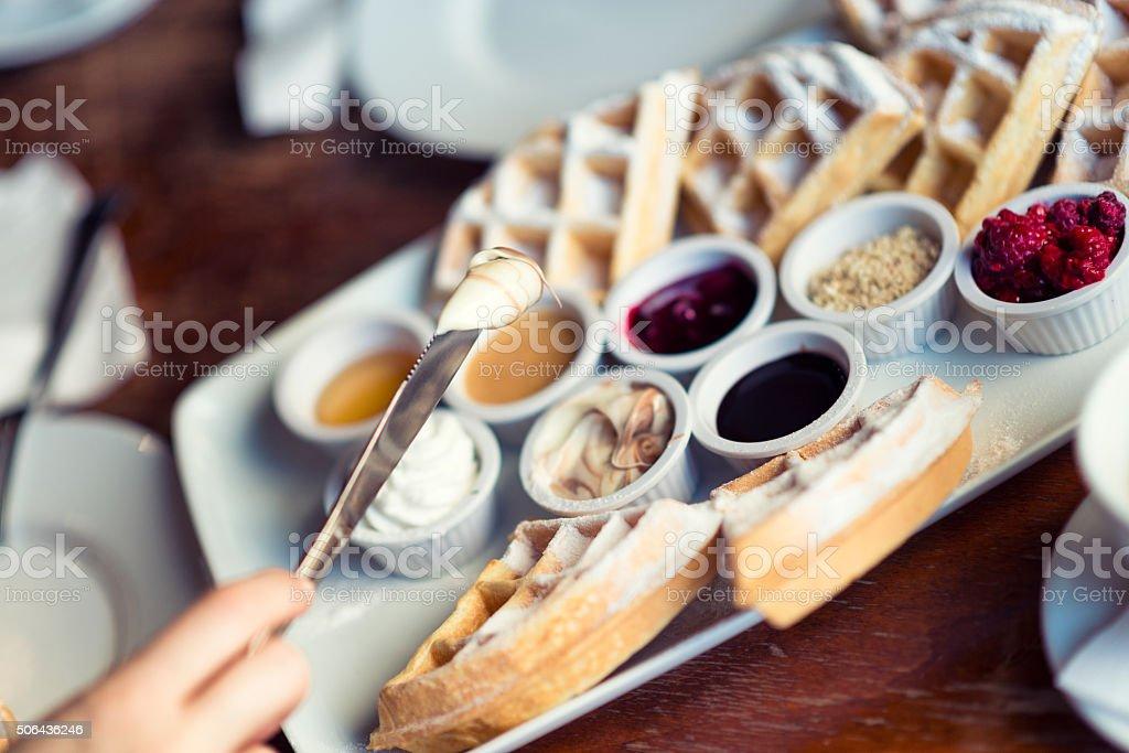 Femme met crème au chocolat à la main sur des gaufres belges - Photo