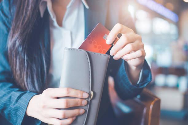 frauen hand mit einer kreditkarte, sie zog die karte aus ihrer brieftasche. - karte ziehen stock-fotos und bilder