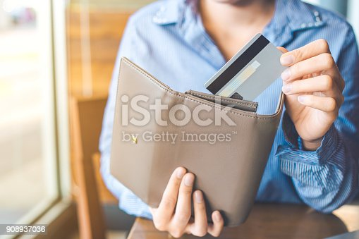istock Women's hand Using a credit card, she pulled the card out of her wallet. 908937036