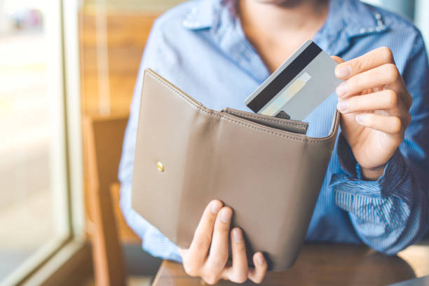 women's hand using a credit card, she pulled the card out of her wallet. - wallet stock pictures, royalty-free photos & images